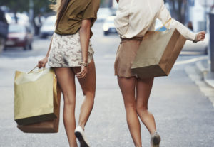 Two young women walking down the street with shopping bags